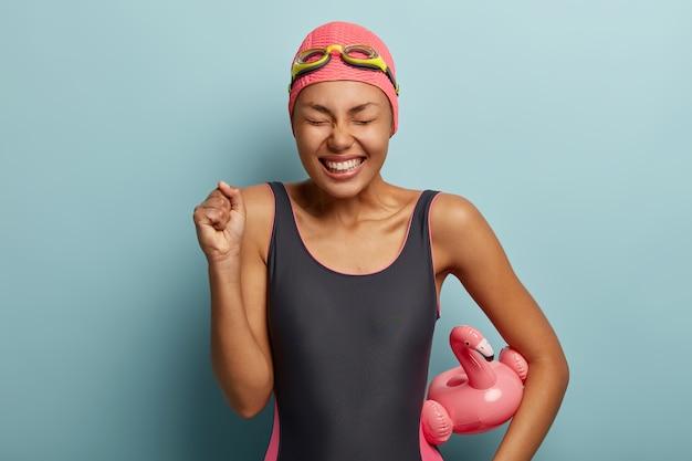 Mulher nadadora feliz e triunfante mantém o punho cerrado, comemora a vitória na competição, mantém os olhos fechados, segura flamigo inflado, usa maiô