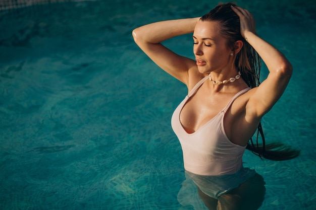 Mulher nadando na piscina azul