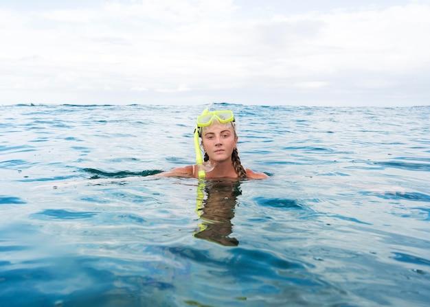 Mulher nadando no oceano com equipamento de mergulho