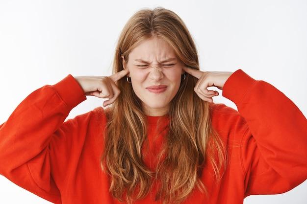 Mulher não consegue se concentrar em um dormitório barulhento fechando os olhos e ouvidos com os dedos indicadores franzindo a testa e franzindo os lábios de aborrecimento e irritação esperando o ruído desaparecer, posando irritada sobre a parede cinza