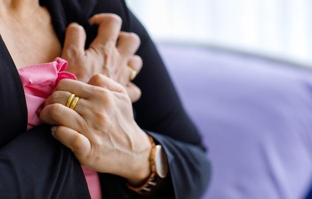 Mulher não identificada, sentada na cama, sofrendo de ataque cardíaco súbito e segurando o peito. conceito de cuidados de saúde de emergência e afetados pela ressuscitação cardiopulmonar, problema cardíaco.