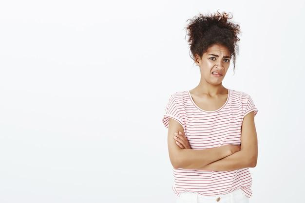 Mulher não impressionada e enojada com penteado afro posando no estúdio