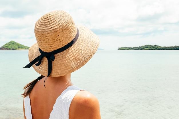 Mulher nas férias de verão, apreciando a vista para o oceano