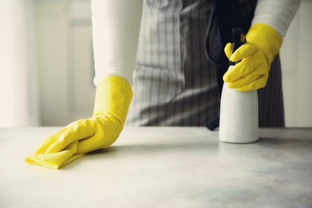 Mulher nas luvas protetoras de borracha amarelas que limpam a poeira e sujas.