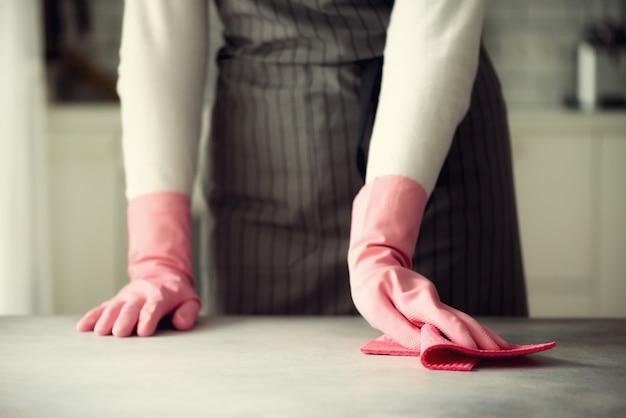 Mulher nas luvas protetoras de borracha cor-de-rosa que limpam a poeira e sujas.