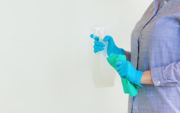 Mulher nas luvas protetoras que limpam a poeira usando um pulverizador e um espanador ao limpar sua casa.
