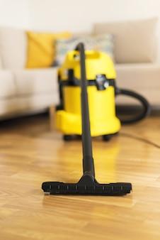 Mulher nas luvas protetoras que limpam a sala de visitas com o aspirador de p30 amarelo. conceito limpo