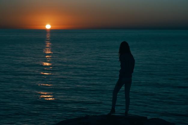 Mulher nas montanhas ao pôr do sol perto do mar ergueu as mãos