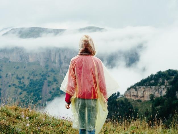 Mulher nas montanhas com uma capa sobre os ombros e a natureza de névoa de ar fresco de montanhas. foto de alta qualidade