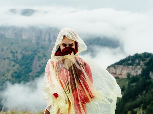 Mulher nas montanhas com uma capa sobre os ombros e a natureza de névoa de ar fresco de montanhas.