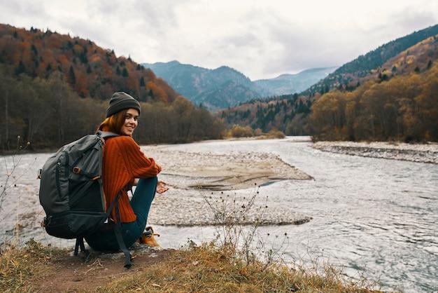 Mulher nas montanhas no outono com uma mochila sentada na margem do rio e olhando para o alto