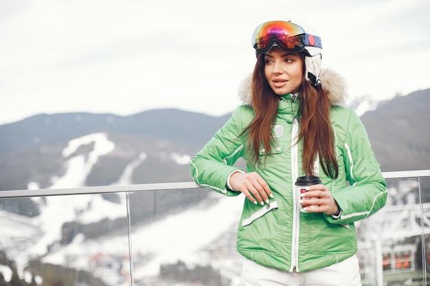 Mulher nas montanhas num dia de inverno. senhora com um uniforme de esqui.