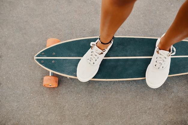 Mulher nas sapatilhas que montam o skate ao ar livre na superfície do asfalto.
