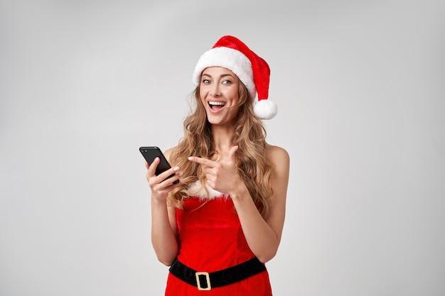 Mulher natal chapéu de papai noel branco fundo de estúdio com smartphone na mão