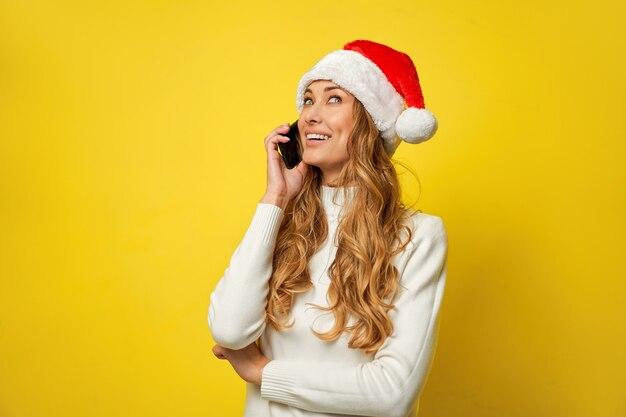 Mulher natal chapéu de papai noel com parede amarela com smartphone na mão