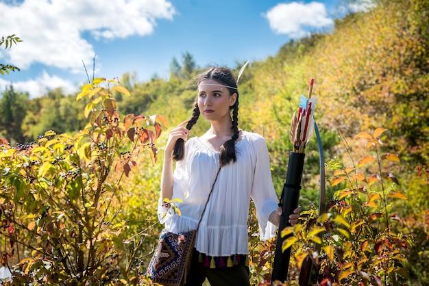 Mulher nativa americana segurando arco e flecha, posando para a natureza. estilo de vida