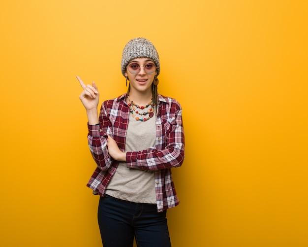 Mulher natural jovem hippie, apontando para o lado com o dedo
