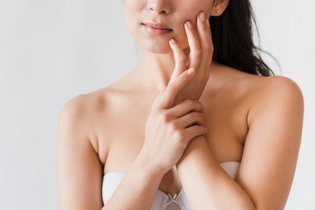 Mulher natural sensual no rosto tocar o sutiã
