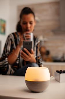 Mulher navegando no telefone desfrutando de aromaterapia com difusor de óleo essencial