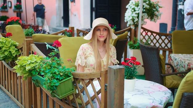 Mulher navegando smartphone fora do café mulher alegre sentada à mesa no restaurante do lado de fora e ...