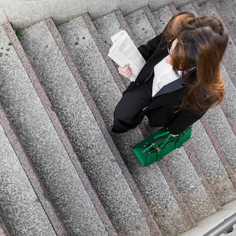 Mulher negócio, com, jornal, e, saco, andar escadas