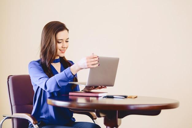 Mulher negócio, em, escritório, atrás de, laptop