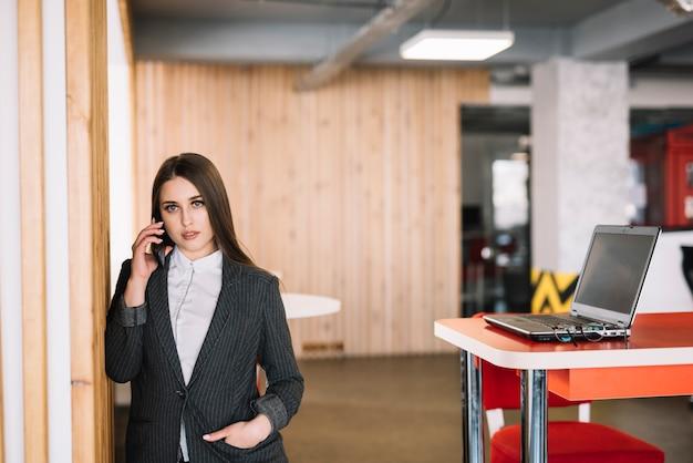 Mulher negócio, falando por telefone, em, parede, em, escritório
