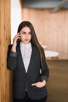 Mulher negócio, falando por telefone, em, parede