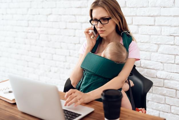 Mulher negócio, falando, telefone, e, segurando, recém-nascido