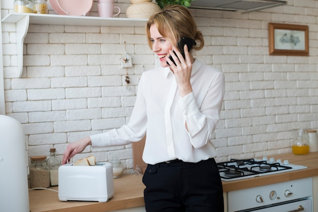 Mulher negócio, falando telefone, enquanto, fazendo, brindes