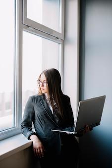 Mulher negócio, ficar, em, janela, com, laptop