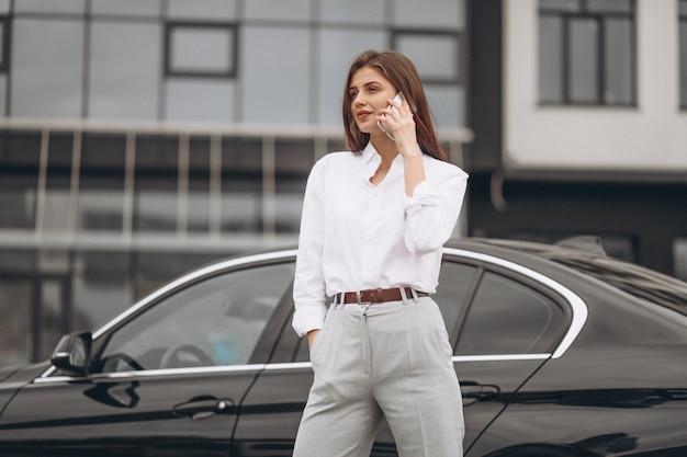 Mulher negócio, ficar, por, a, car, e, usando, telefone