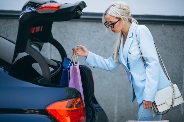 Mulher negócio, pôr, bolsas compras, carro