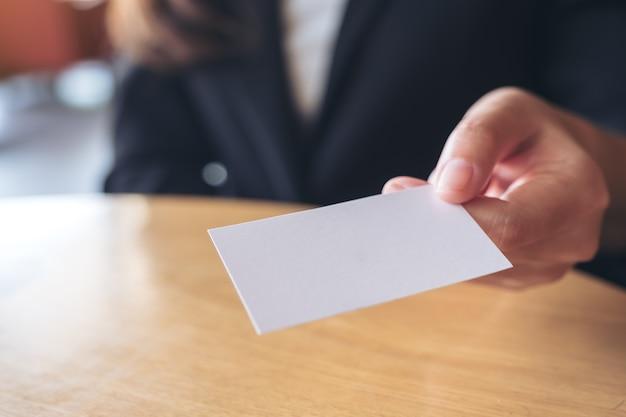 Mulher negócio, segurando, e, dar, um, vazio, cartão negócio, para, alguém, ligado, tabela, em, escritório