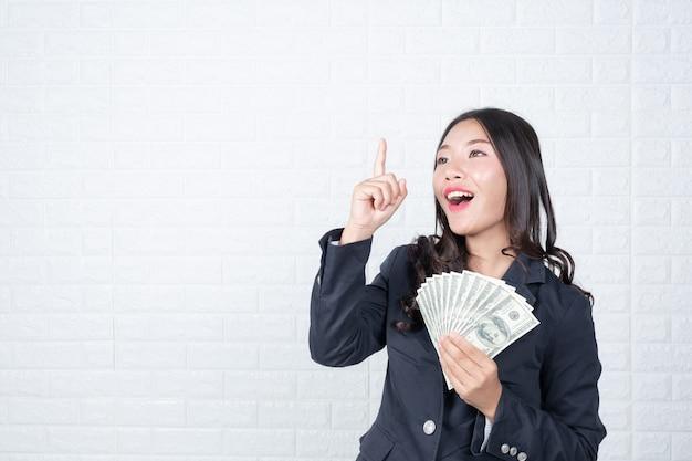 Mulher negócio, segurando, nota, dinheiro, separadamente, branca, parede tijolo, feito, gestos, com, sinal, language.