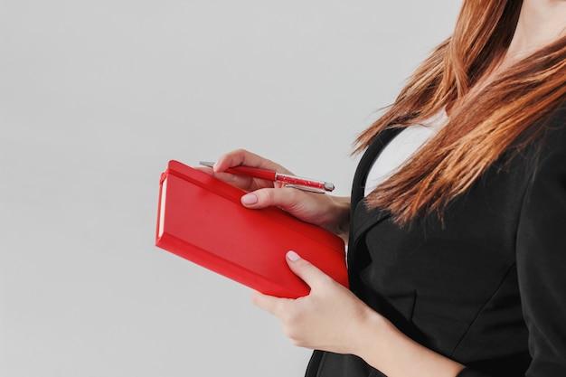 Mulher negócio, senhora, em, terno preto, com, vermelho, diário, planejador, em, mão