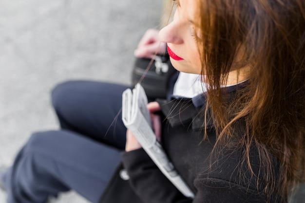 Mulher negócio, sentando, com, jornal, exterior