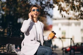 Mulher negócio, sentando, ligado, um, banco, com, telefone, café bebendo