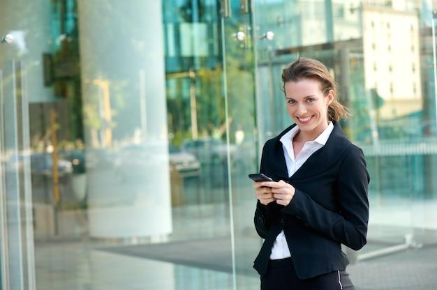 Mulher negócio, sorrindo, com, telefone pilha, exterior, edifício escritório