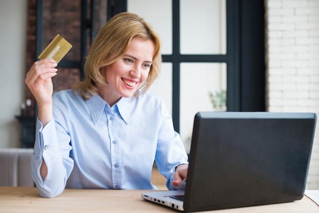 Mulher negócio, usando computador portátil, e, cartão crédito
