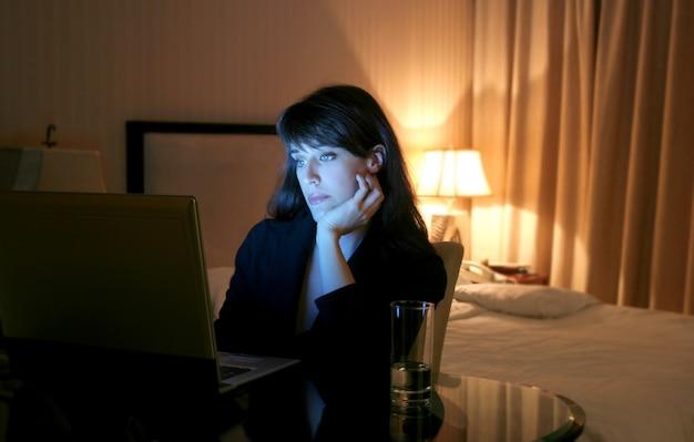 Mulher negócio, usando computador portátil, em, um, quarto hotel