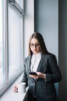 Mulher negócio, usando, smartphone, em, janela