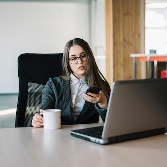 Mulher negócio, usando, smartphone, tabela
