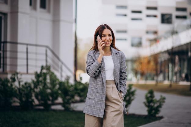 Mulher negócio, usando, telefone, rua, em, a, rua, por, a, predios