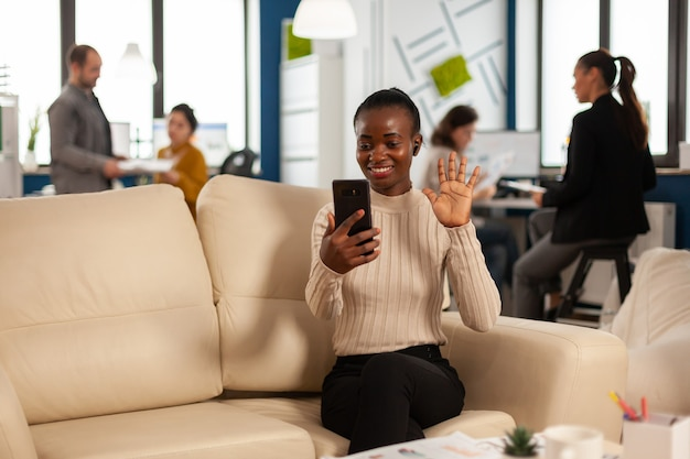 Mulher negra acenando para a câmera e explicando relatórios financeiros para o gerente remoto na videochamada segurando um smartphone usando fones de ouvido, sentado no sofá