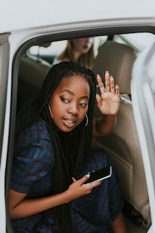 Mulher negra acenando para se despedir de um carro
