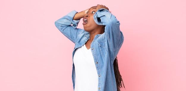 Mulher negra adulta afro com a boca aberta, parecendo horrorizada e chocada por causa de um erro terrível, levando as mãos à cabeça