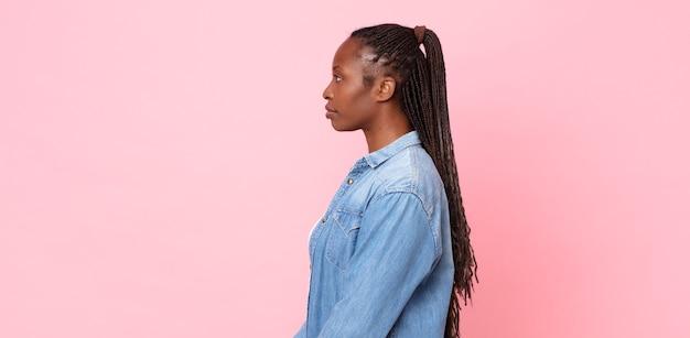 Mulher negra adulta afro em vista de perfil olhando para copiar o espaço à frente, pensando, imaginando ou sonhando acordada