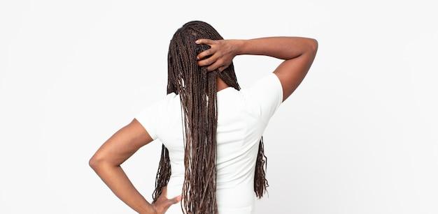 Mulher negra adulta afro pensando ou duvidando, coçando a cabeça, sentindo-se perplexa e confusa, visão traseira ou traseira