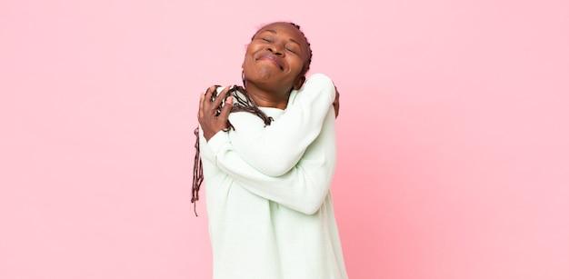 Mulher negra adulta afro se sentindo apaixonada, sorrindo, acariciando e se abraçando, permanecendo solteira, sendo egoísta e egocêntrica